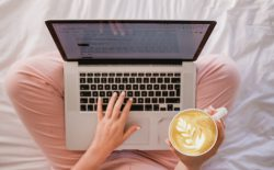 woman typing on laptop with coffee