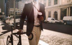 man walking with bike and coffee